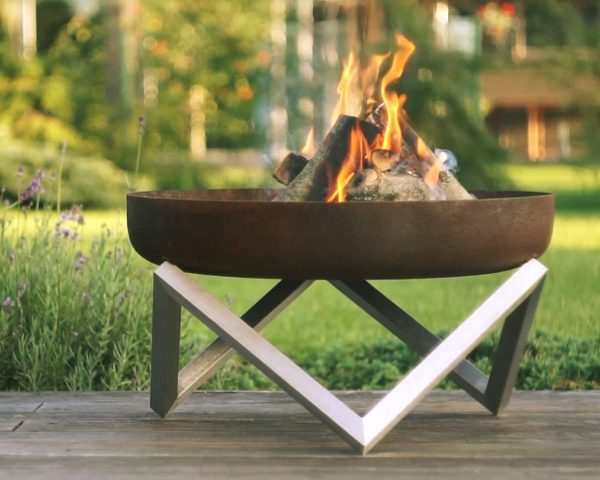 modern fire pit with burning wood logs on the patio