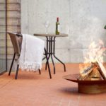 Curonian Gile Wood Burning rusting steel Fire Pit on the pavement near the table and chair