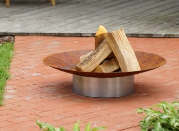 Curonian Gile Wood Burning Fire Pit combination of rusting and stainless steel on the pavement