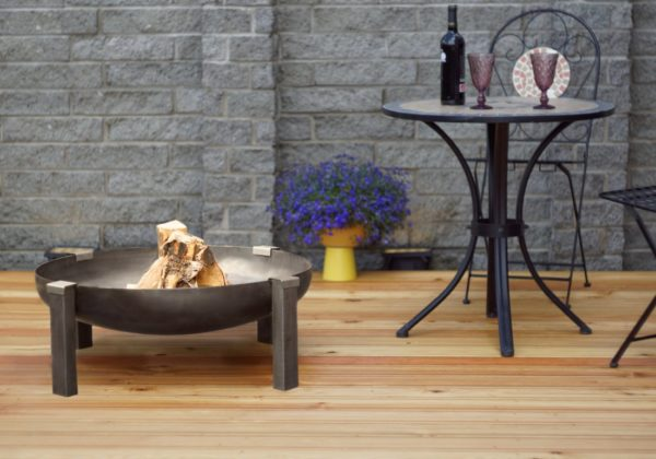 Tilsit wood burning rusting steel fire pit on the patio near the table with wine bottle and glasses
