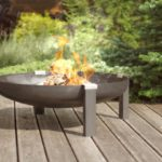 Tilsit wood burning rusting steel fire pit on the patio with burning fire