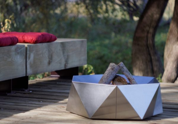 Junda wood-burning stainless steel fire pit on the patio near the bench with red cushions