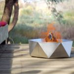 Junda wood-burning stainless steel fire pit with fire on the patio near the bench with red cushions